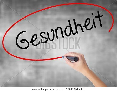 Woman Hand Writing Gesundheit (health In German)  With Black Marker Over Transparent Board.