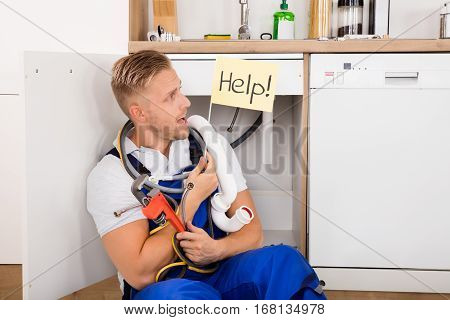 Young Male Plumber Holding Flag With Help Text In Kitchen