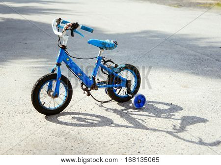 Old children's bicycle. Old blue bicycle tricycle. Morally old.