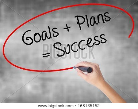 Woman Hand Writing Goals + Plans = Success With Black Marker Over Transparent Board.