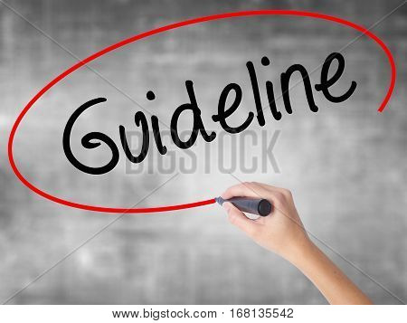 Woman Hand Writing Guideline With Black Marker Over Transparent Board