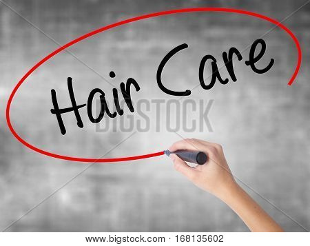 Woman Hand Writing  Hair Care With Black Marker Over Transparent Board