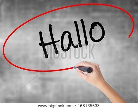 Woman Hand Writing Hallo  (hello In German) With Black Marker Over Transparent Board