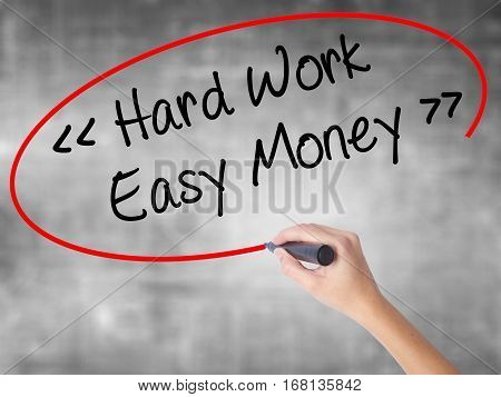 Woman Hand Writing Hard Work - Easy Money With Black Marker Over Transparent Board.