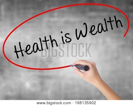 Woman Hand Writing Health Is Wealth With Black Marker Over Transparent Board