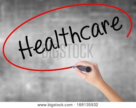 Woman Hand Writing Healthcare With Black Marker Over Transparent Board