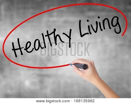 Woman Hand Writing Healthy Living  With Black Marker Over Transparent Board