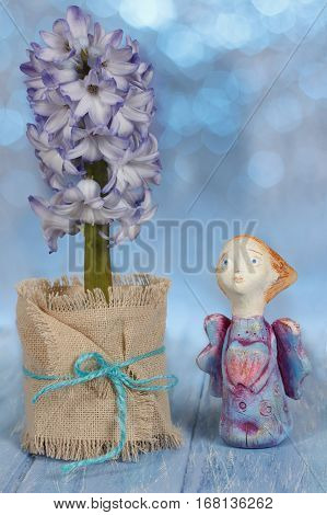 Greeting card with handmade clay angel and hyacinth flower in pot on blue wooden table on bokeh background. Valentine's day wedding easter or birthday concept.