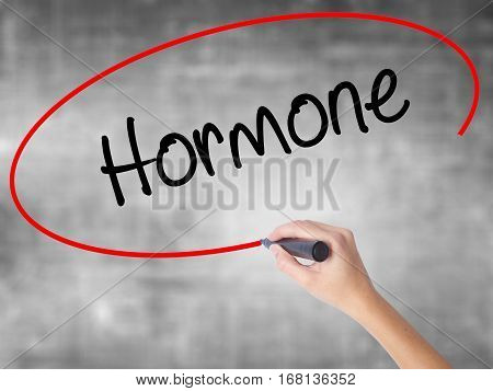 Woman Hand Writing Hormone With Black Marker Over Transparent Board