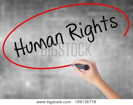 Woman Hand Writing Human Rights With Black Marker Over Transparent Board