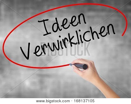 Woman Hand Writing Ideen Verwirklichen ( Realize Ideas In German) With Black Marker Over Transparent