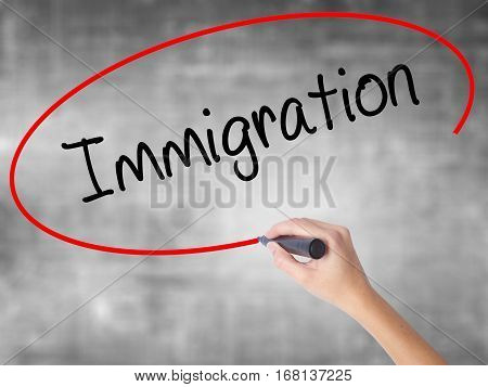 Woman Hand Writing Immigration With Black Marker Over Transparent Board