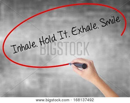 Woman Hand Writing Inhale Hold It Exhale Smile With Black Marker Over Transparent Board