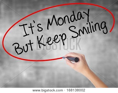 Woman Hand Writing It's Monday But Keep Smiling With Black Marker Over Transparent Board
