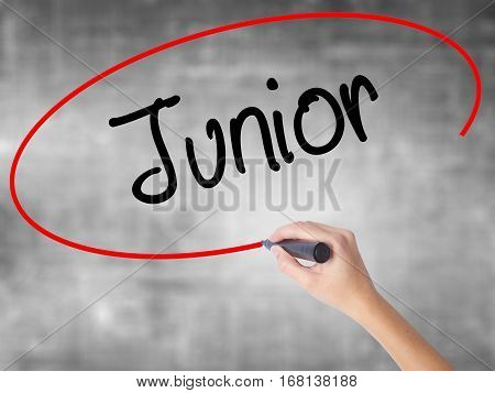 Woman Hand Writing Junior With Black Marker Over Transparent Board