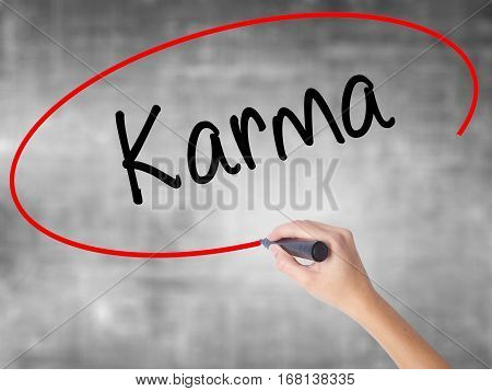 Woman Hand Writing Karma  With Black Marker Over Transparent Board