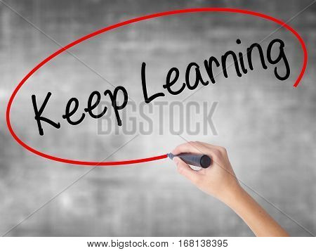 Woman Hand Writing Keep Learning With Black Marker Over Transparent Board
