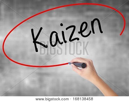 Woman Hand Writing Kaizen With Black Marker Over Transparent Board