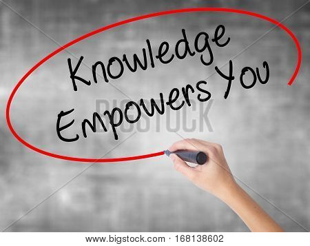Woman Hand Writing Knowledge Empowers You With Black Marker Over Transparent Board
