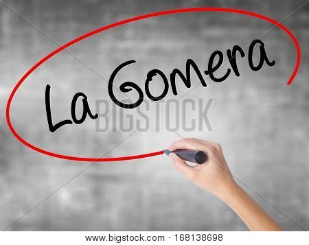 Woman Hand Writing La Gomera With Black Marker Over Transparent Board.