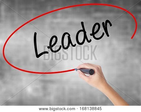 Woman Hand Writing Leader With Black Marker Over Transparent Board