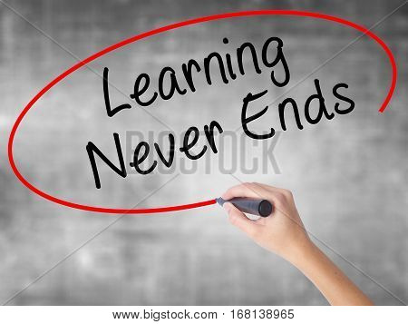 Woman Hand Writing Learning Never Ends With Black Marker Over Transparent Board
