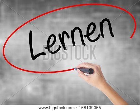 Woman Hand Writing Lernen (learn In German) With Black Marker Over Transparent Board.