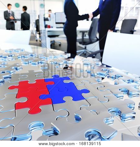 Conceptual business image. Puzzle pieces on meeting table at busy modern office.