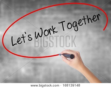 Woman Hand Writing Lets Work Together With Black Marker Over Transparent Board