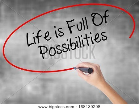 Woman Hand Writing Life Is Full Of Possibilities With Black Marker Over Transparent Board