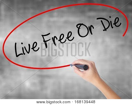 Woman Hand Writing Live Free Or Die With Black Marker Over Transparent Board.