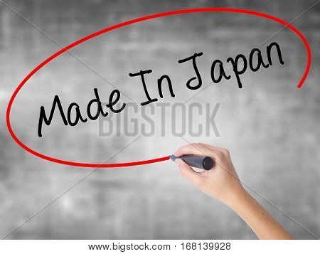 Woman Hand Writing Made In Japan With Black Marker Over Transparent Board