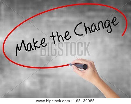 Woman Hand Writing Make The Change With Black Marker Over Transparent Board