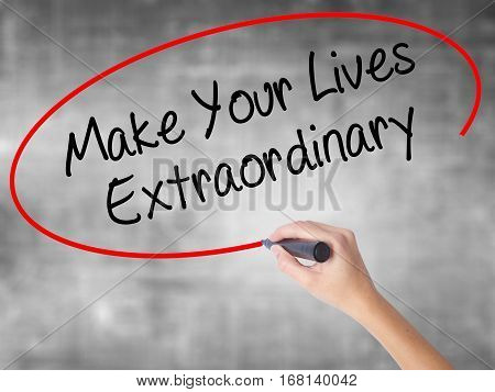 Woman Hand Writing Make Your Lives Extraordinary With Black Marker Over Transparent Board