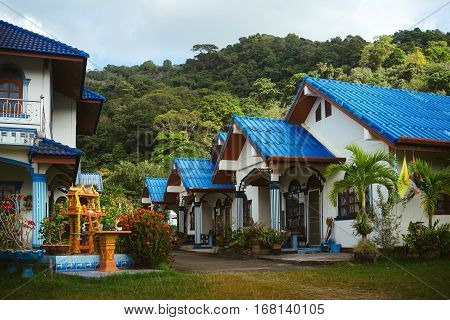 House with blue roof. Street with one-story houses. Cute one-storey houses. Modern Thai house. Floors house. House on a background of mountains.