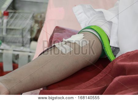 Blood donor in arm injection select focus with shallow depth of field.