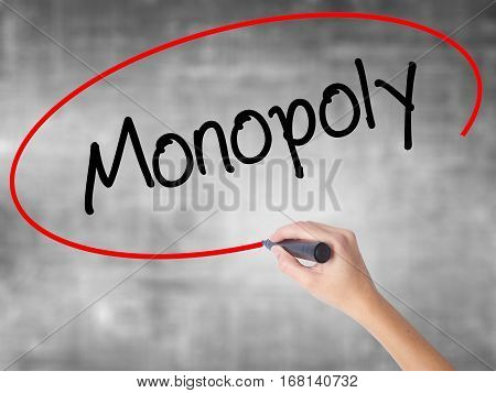 Woman Hand Writing Monopoly With Black Marker Over Transparent Board.