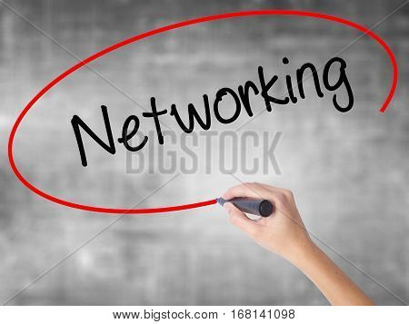 Woman Hand Writing Networking With Black Marker Over Transparent Board