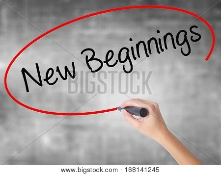 Woman Hand Writing New Beginnings With Black Marker Over Transparent Board