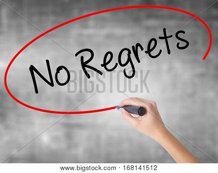 Woman Hand Writing No Regrets With Black Marker Over Transparent Board