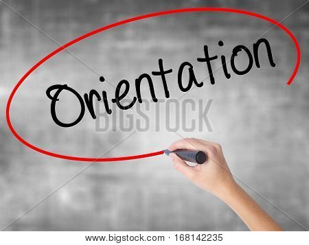 Woman Hand Writing Orientation With Black Marker Over Transparent Board