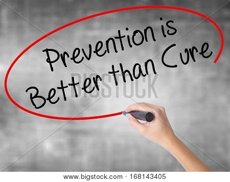 Woman Hand Writing Prevention Is Better Than Cure With Black Marker Over Transparent Board