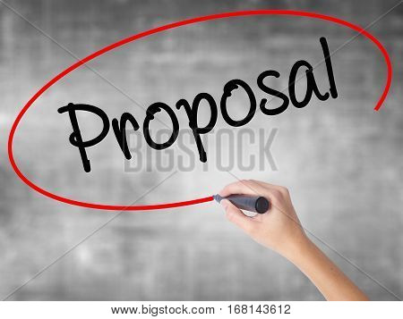 Woman Hand Writing  Proposal With Black Marker Over Transparent Board