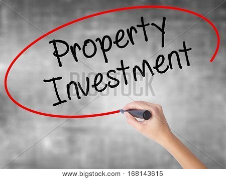 Woman Hand Writing Property Investment With Black Marker Over Transparent Board