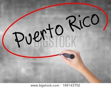 Woman Hand Writing Puerto Rico With Black Marker Over Transparent Board