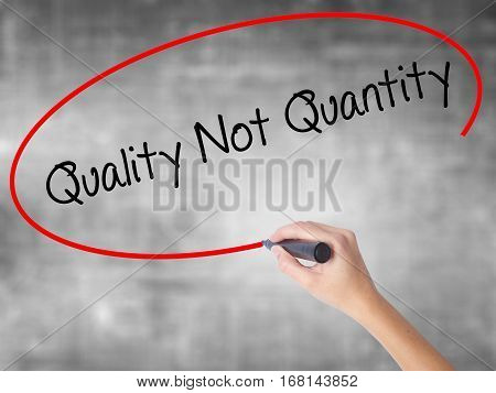 Woman Hand Writing Quality Not Quantity With Black Marker Over Transparent Board