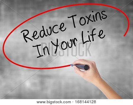 Woman Hand Writing Reduce Toxins In Your Life With Black Marker Over Transparent Board