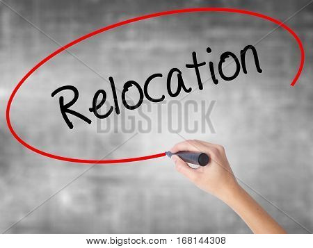 Woman Hand Writing Relocation  With Black Marker Over Transparent Board