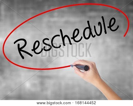Woman Hand Writing Reschedule  With Black Marker Over Transparent Board