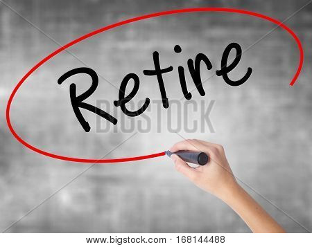 Woman Hand Writing Retire With Black Marker Over Transparent Board